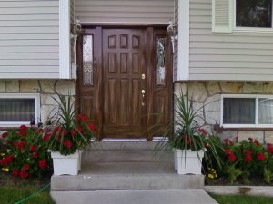 This exterior nine-panel door with side panel has been woodgrained to match the colors of the exterior paneling and stone.