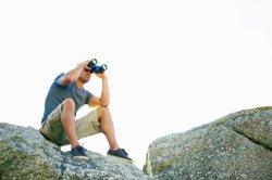 Outdoorsman Using Binoculars and Eye Shields