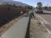 A work crew does the finish work on a concrete sidewalk.