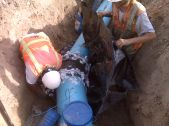 Two men in construction vests repair a broken pipe in a trench.