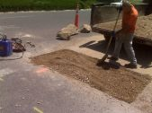 A worker uses a shovel to smooth dirt that fills a hole cut into concrete to make a repair.