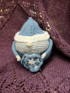 Round gnome holding a knitted snowflake