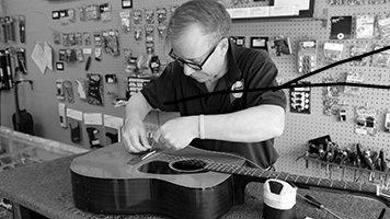 TJ Peavey restringing a guitar
