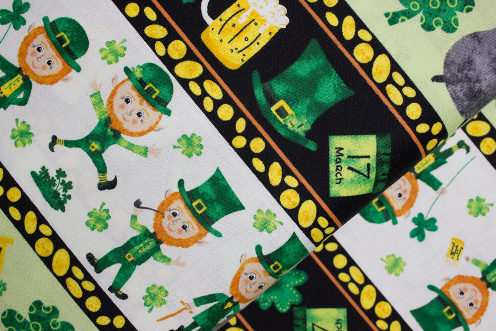 SPECIALTY FABRICS:  Leprechaun Border Stripes with Clovers, Beer, Horseshoes, Pots of Gold, and March 17 in Gold, White, Green, and Black:  Spring Jubilee by Alyssa Kays for Blank Quilting