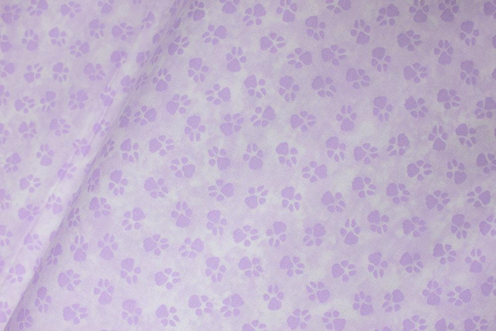 Dog-On-It: Purple Paw Prints on Light Purple by Ann Lauer for Benartex