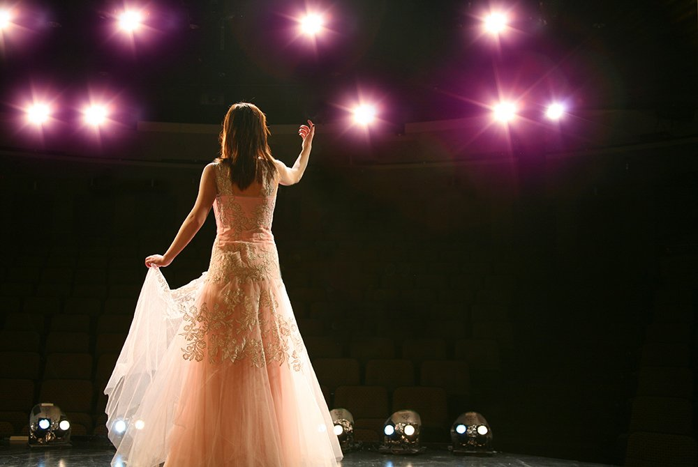 woman performing on stage in pink dress