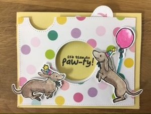 Polka dot card with two dogs holding a balloon that says