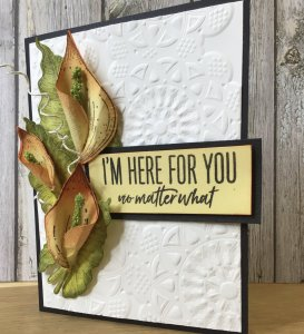 White, embossed card with a flower and banner that says