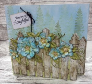 Thoughtful Card With Flowers Growing Through a Fence With Trees in the Background