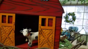 Toy cow looking out of barn