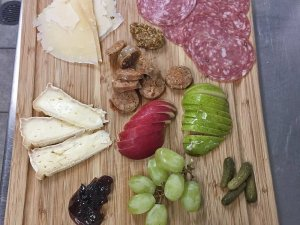 cutting board with fruit and meats