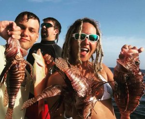 Divers with speared lionfish.