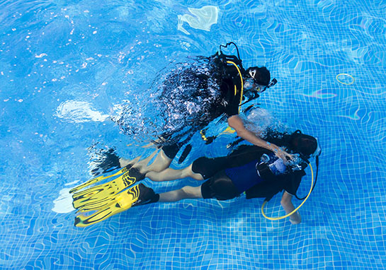 Scuba instructor leading student in pool
