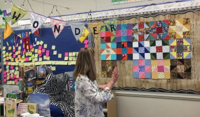 Mrs. Southerland arranges the blocks on the design wall - not quite there yet.