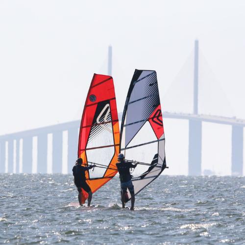 two people windsurfing in front of skyway bridge