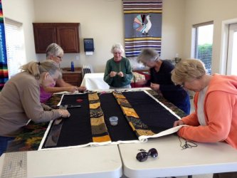 Neighbors Working on a Quilt Together