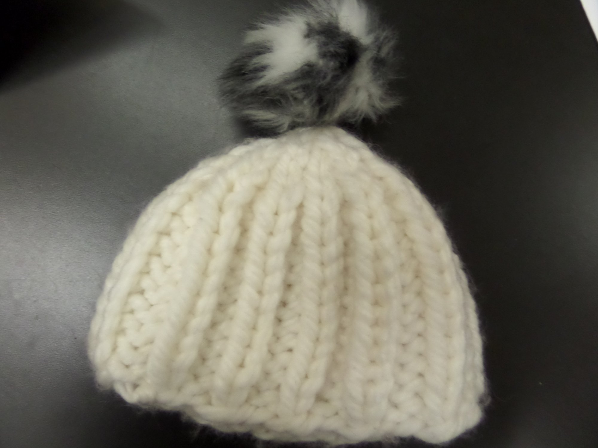 Cabled hat in Poppy yarn from Tahki