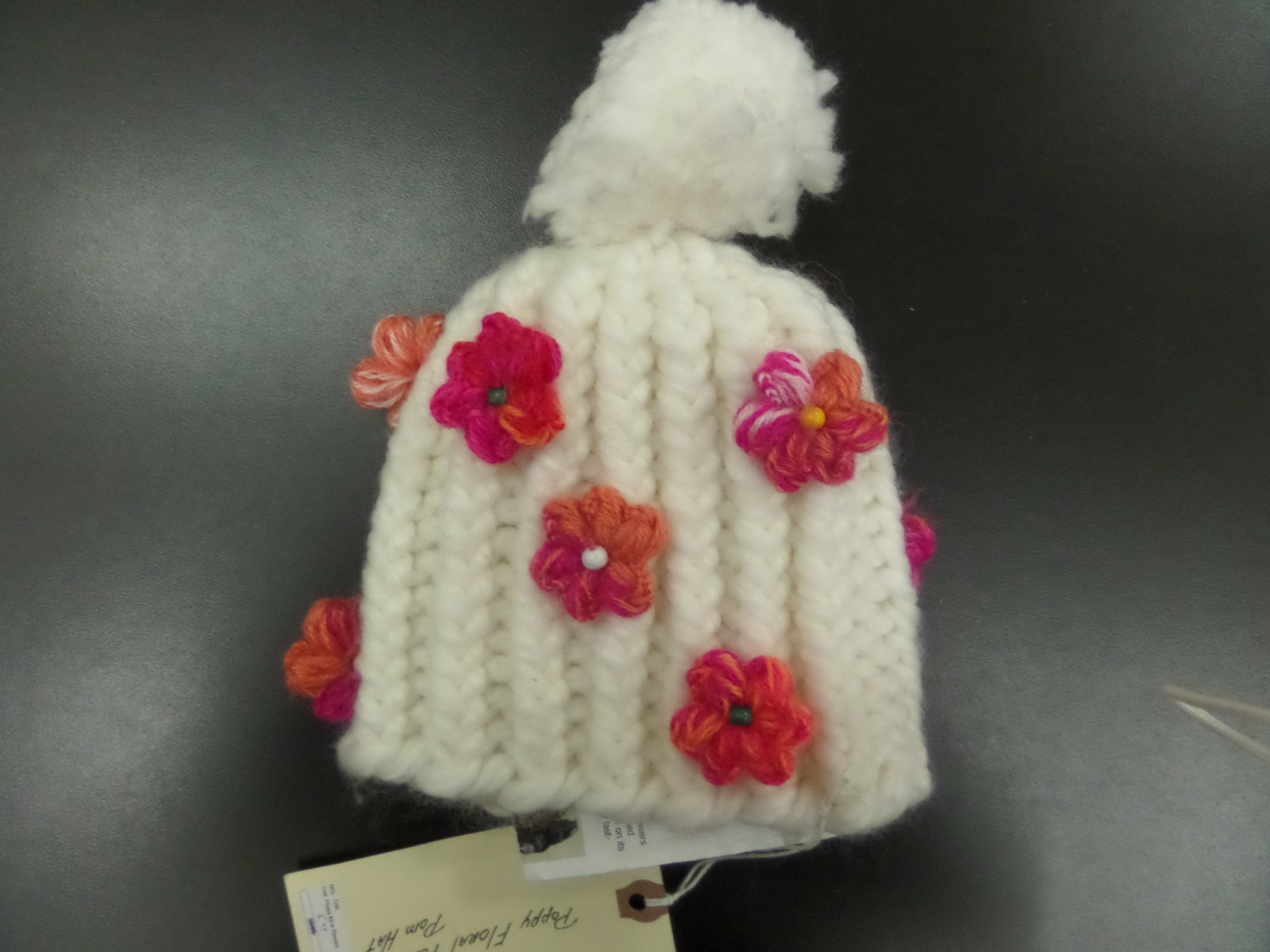 Cabled hat in Poppy yarn with flowers from Tahki