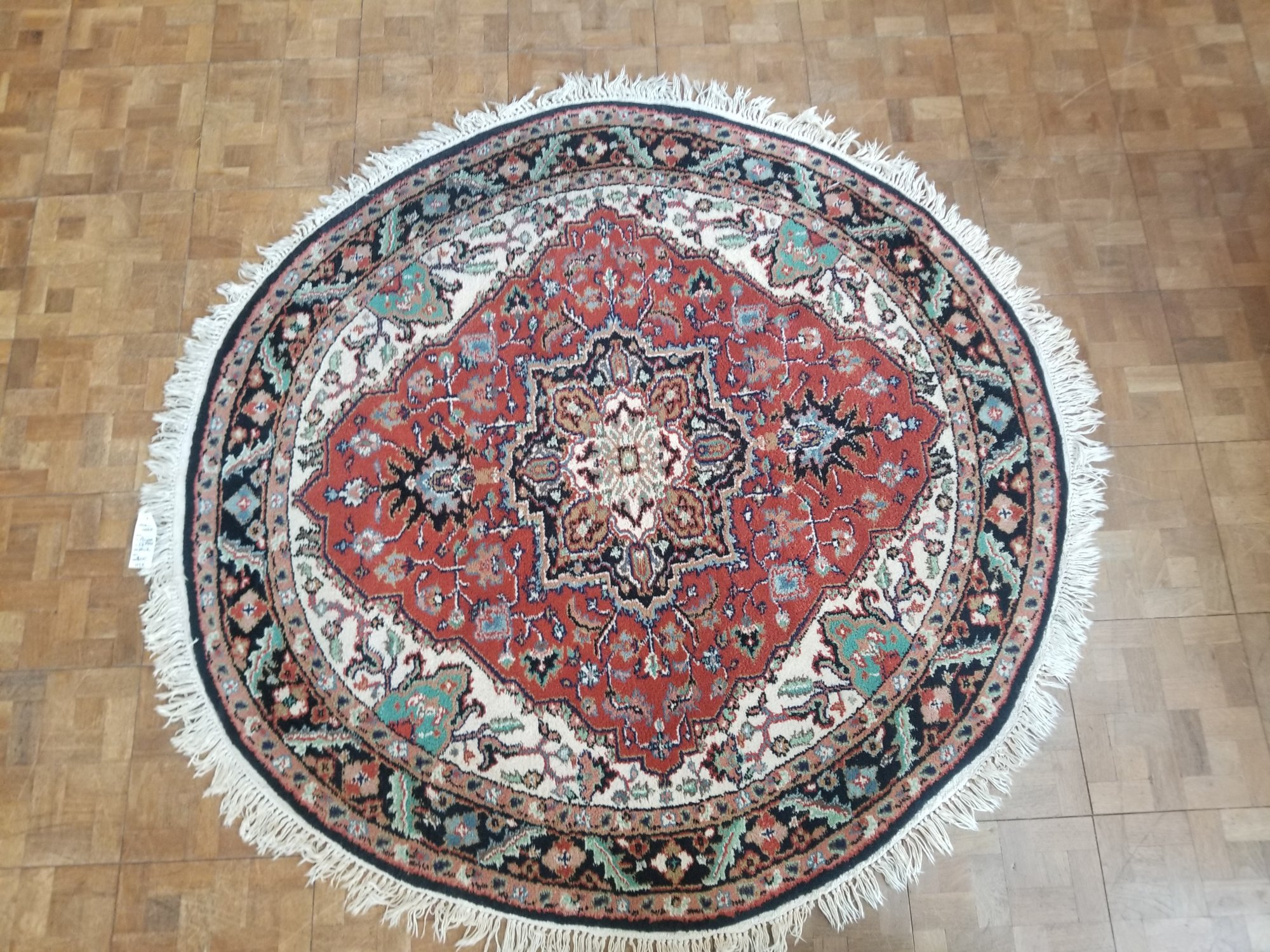 5'6 X 5'6 round Persian Heriz rust red field with a center medallion of cream outlined in black with a black border and many accent colors like grey green taupe and light blue     UTX
