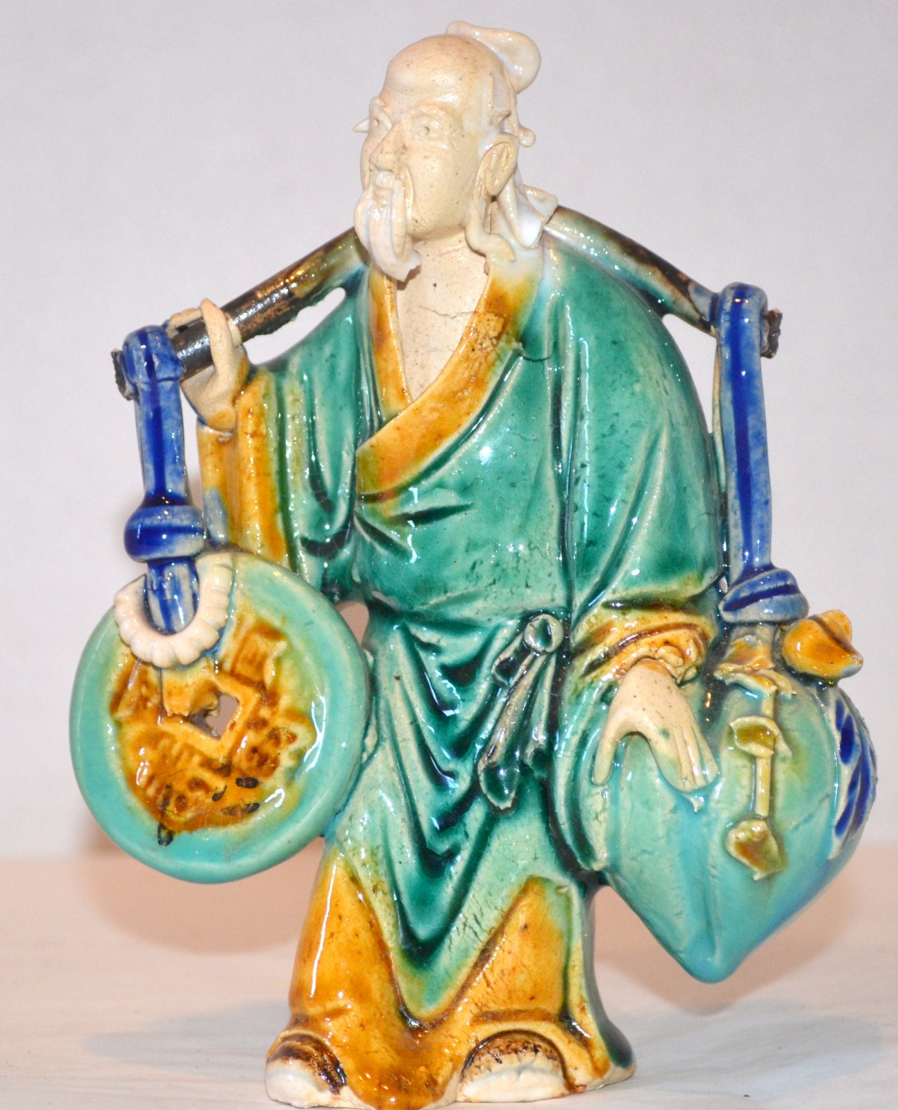 Chinese Mud Man Ceramic with a shoulder yoke carrying money and a peach