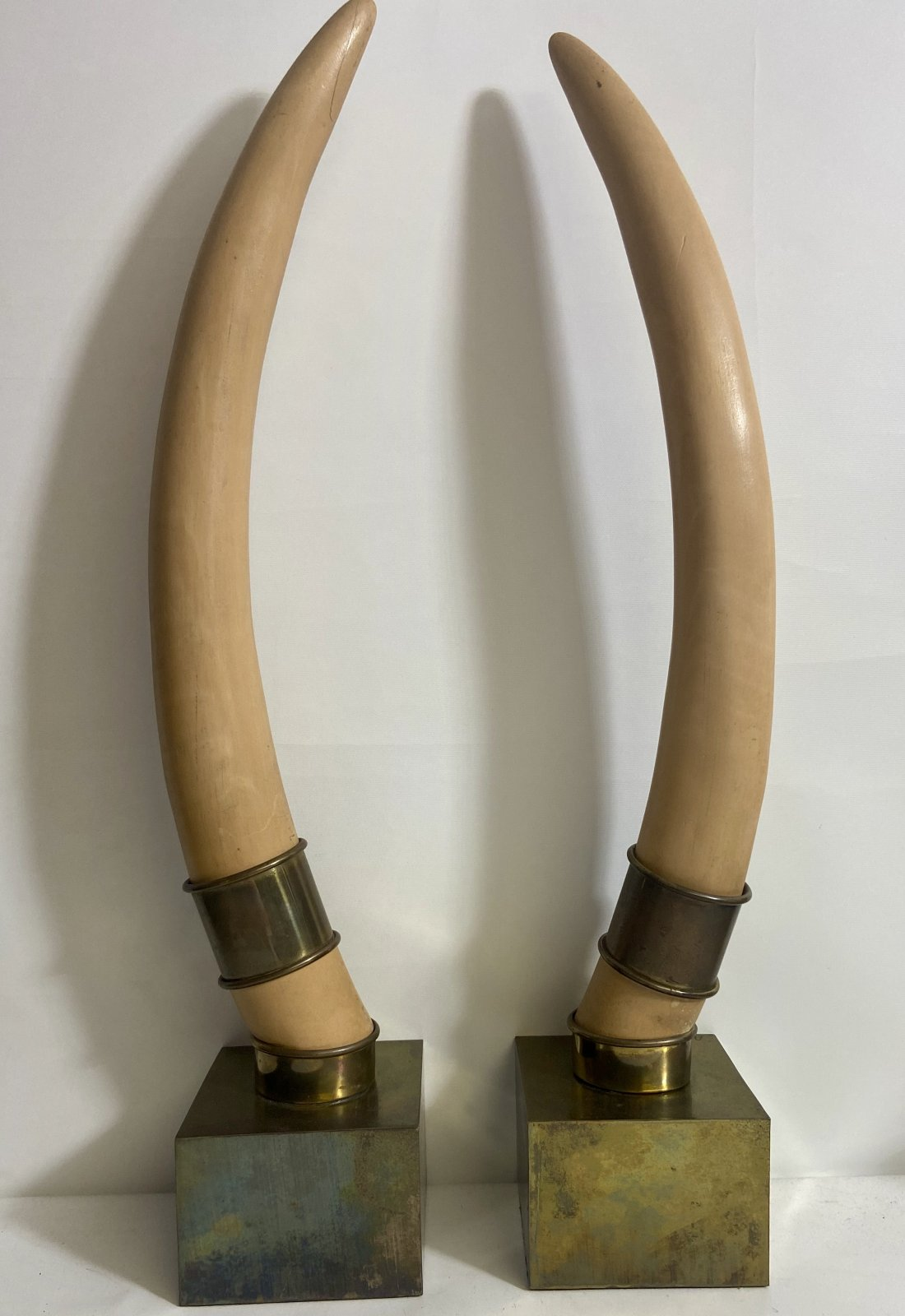Pair of faux tusks by Chapman, decorative resin faux tusks on brass squared bases  UTX