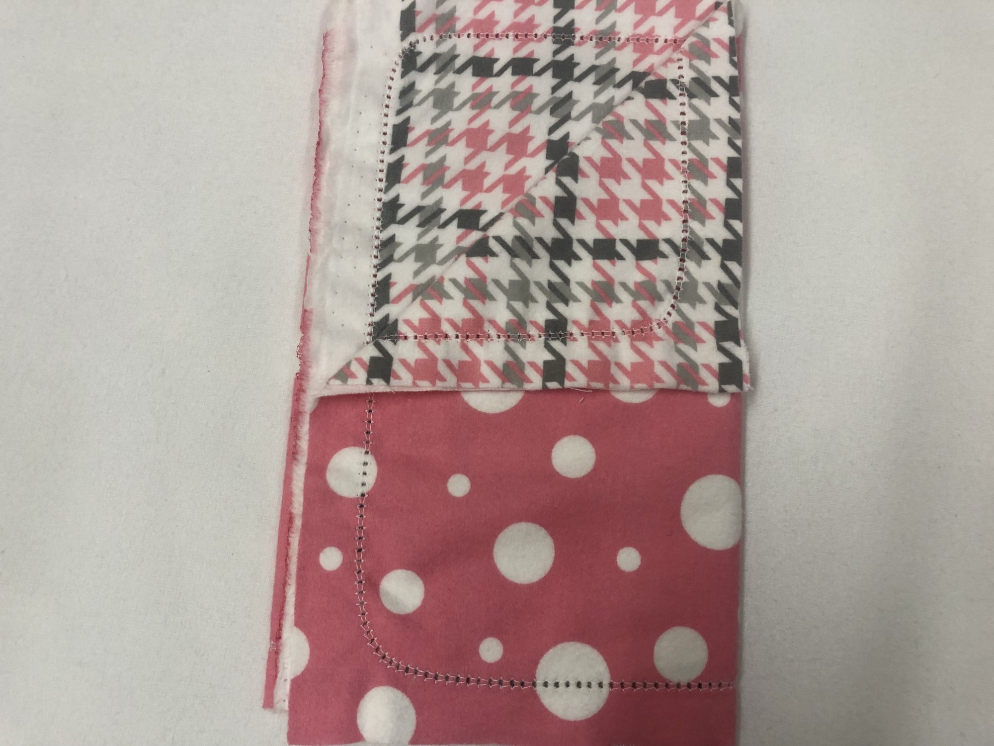 Large white polka dots on pink background with grey/pink houndstooth on white burp