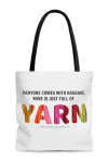 """A white tote bag with a black handle on a white background, with text that reads """"Everyone Comes With Baggage, Mine is Just Full of Yarn"""". The word Yarn is filled with a photo print of multiple colored strands of yarn making a rainbow"""