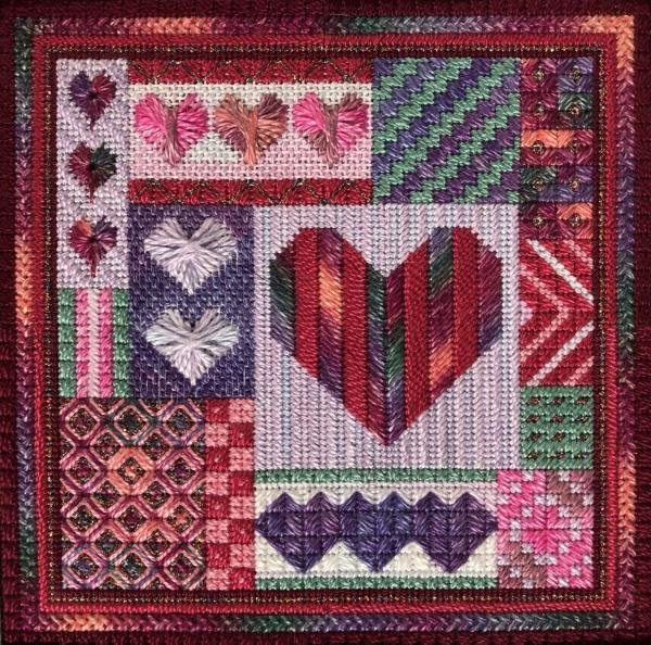 "multicolored ""crazy quilt-like' needlepoint design in a variety of reds and purples and teals"
