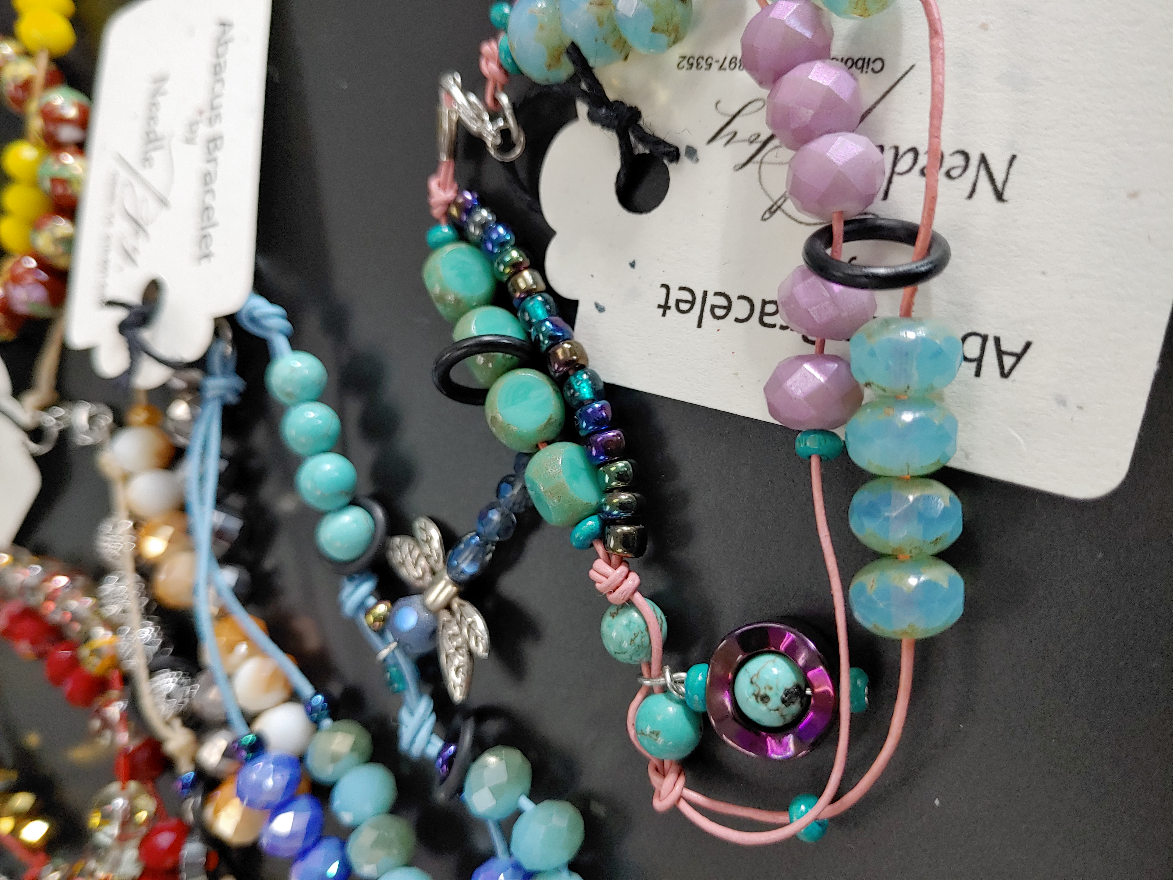 beaded row counter bracelets in various colors, with a pink/blue/purple one in the foreground