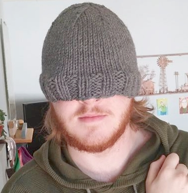 man with grey knitted hat pulled over his eyes