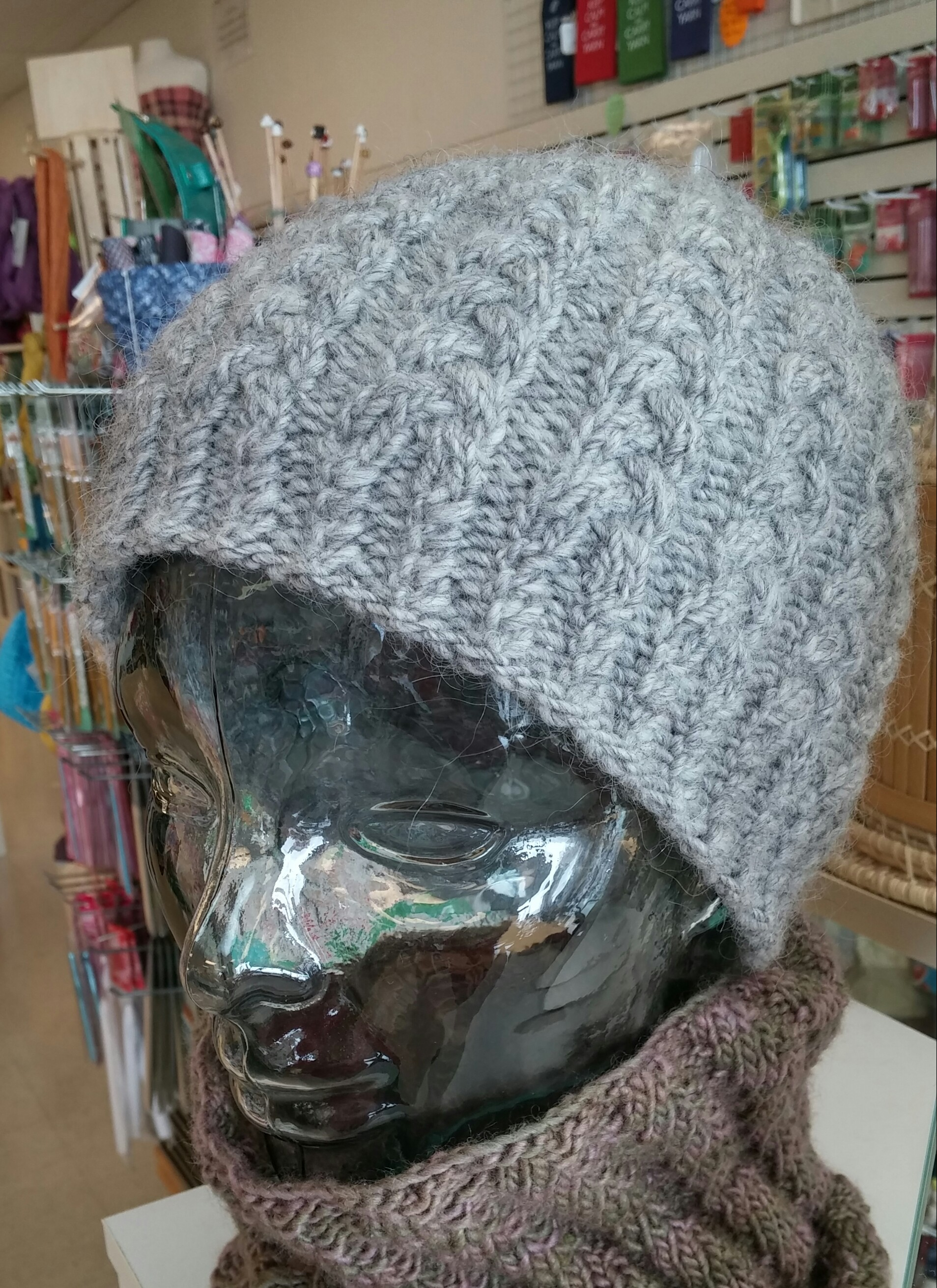 A heathered grey wool hat covered with cables on a glass head form with a wall of knit and crochet notions in the background
