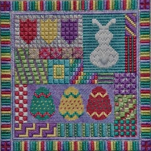 A needlepoint sampler in pastel colors with an easter bunny and several eggs