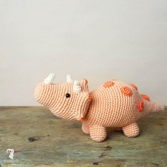 "side-view of cute peach-colored crocheted triceratops with salmon-colored spots standing on a stone ""floor"" with a beige wall in the background."