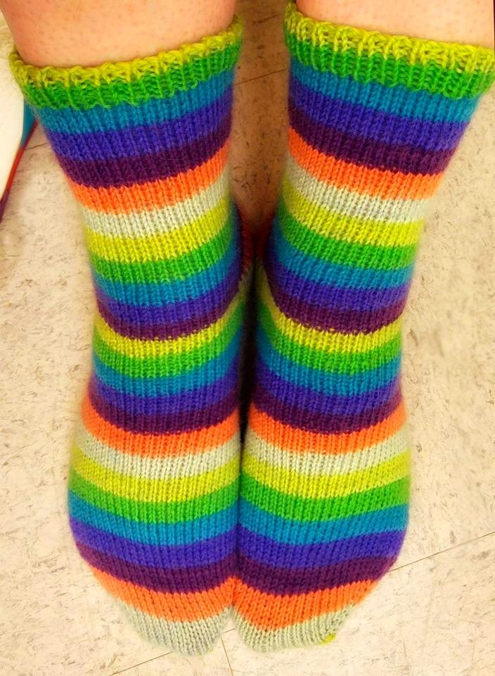 a close up of feet wearing bright colored striped hand knit socks