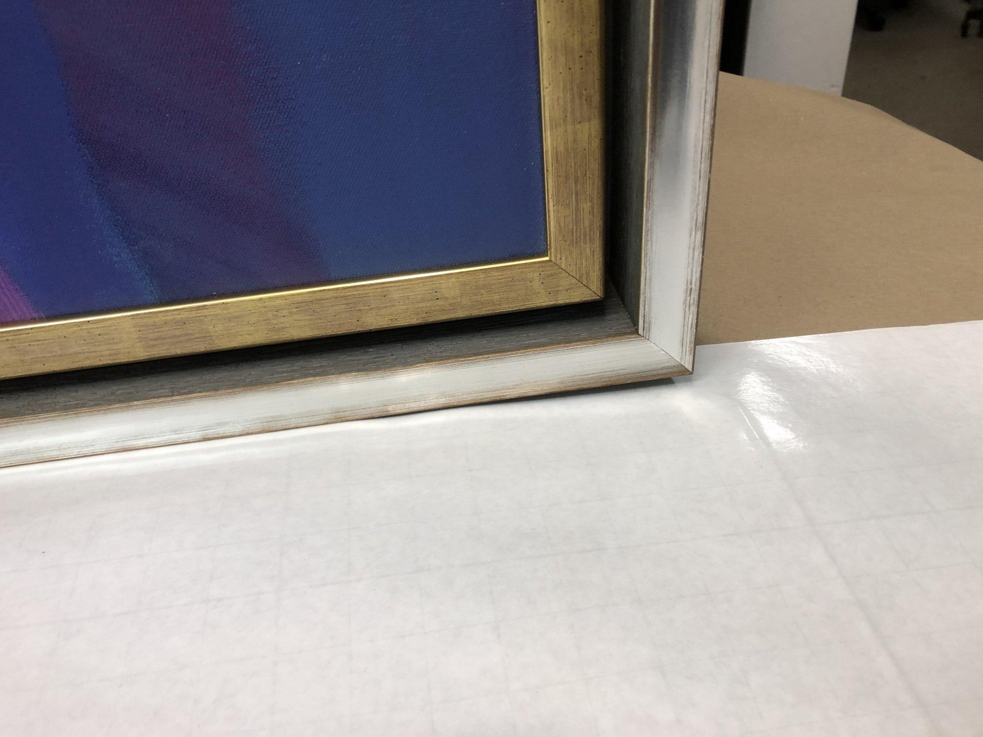 Framed canvas stacked inside floater frame
