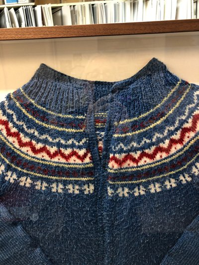 detail of blue cardigan sweater in shadowbox frame