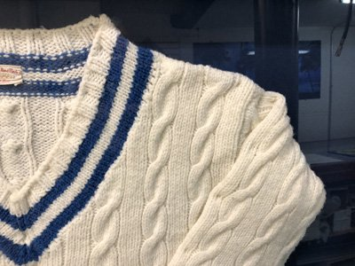 Detail of sleeve in white v-neck sweater shadowbox