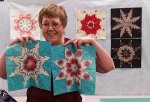 Barb Snider holds two Lemoyne Star quilt blocks she made in class at Quilter's Fancy.