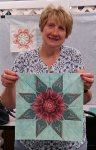 Sue Rohm holds the fussy cut lemoyne star quilt block she made in class at Quilter's Fancy